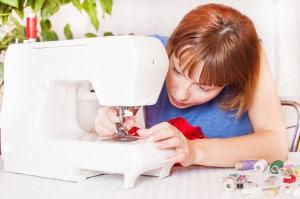 Un sarto che lavora sulla macchina da cucire da casa